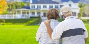 Old Couple Standing in Front of a House