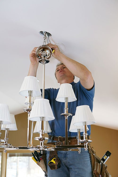handyman fixing a ceiling light fixture