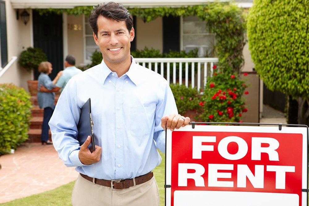 Real Estate agent standing in front of a house