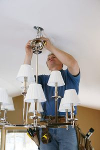 TruBlue handyman fixing a ceiling light fixture