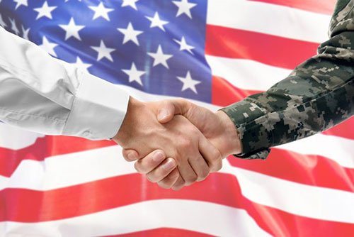 Shaking hands in front of an american flag